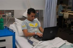 A young man using his laptop in bed while in a clinical trial
